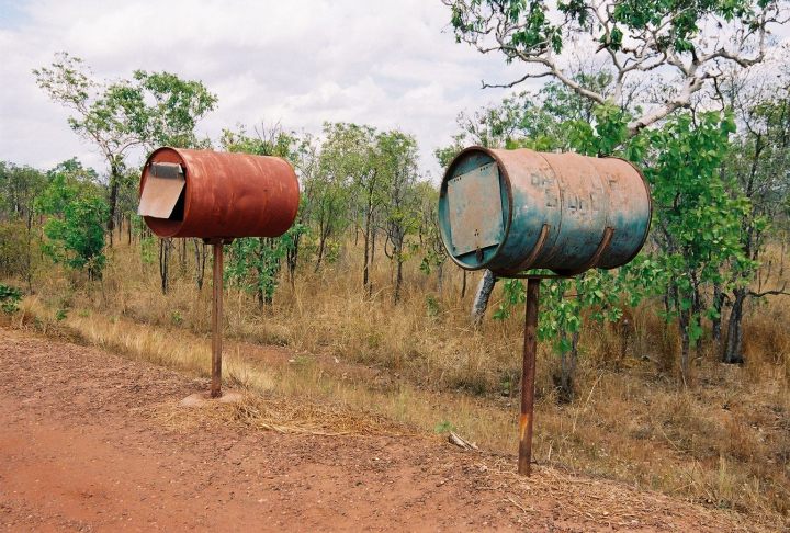 Two mailboxes in the Australian Outback made of old oil drums or barrels.